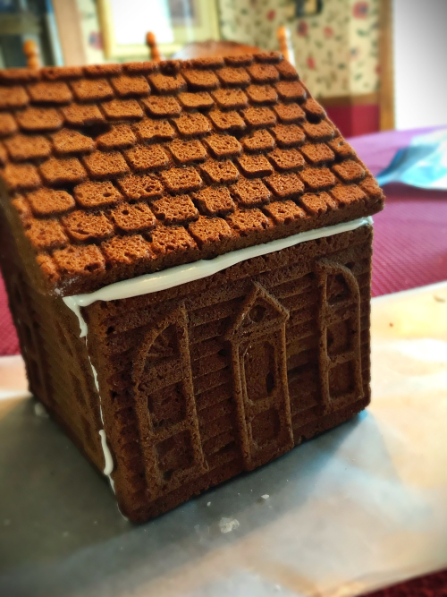 knitted gingerbread house stepping away from the edge